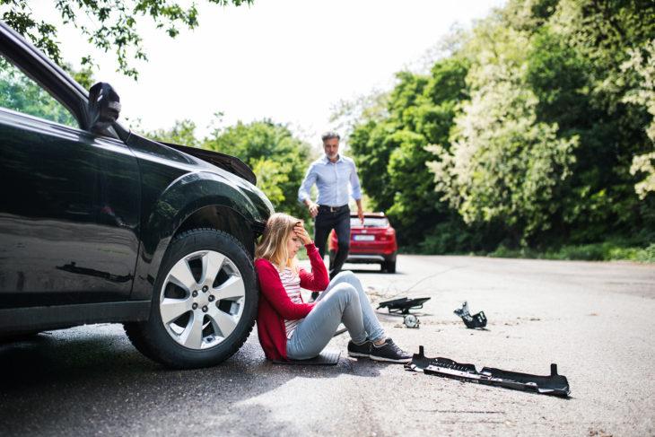Chica sentada en el piso después de haber tenido una accidente automovilístico