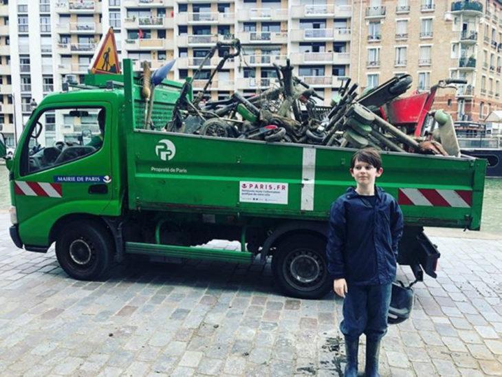 Raphaël delante de un camión que carga la chatarra que sacó del río Sena