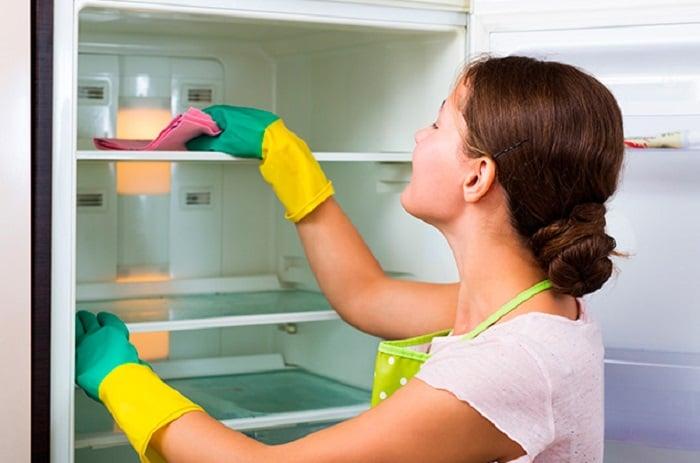 Chica limpiando la nevera