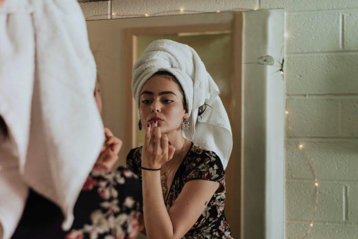 Chica mirándose al espejo y aplicándose balsamo labial