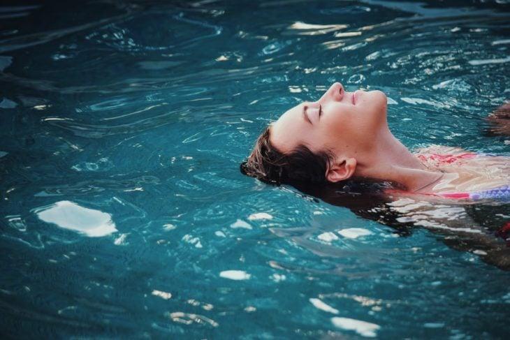 Chica nadando boca arriba y sonriéndo