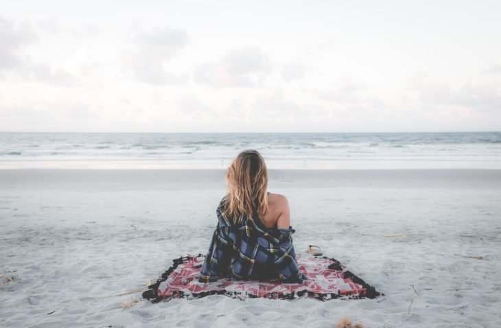 Chica sentada en la playa frente al mar