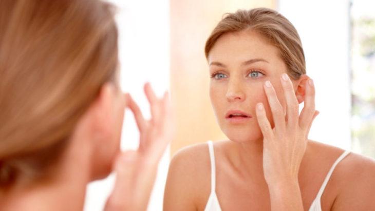 Mujer mirándose en el espejo y viendo si tiene líneas de expresión
