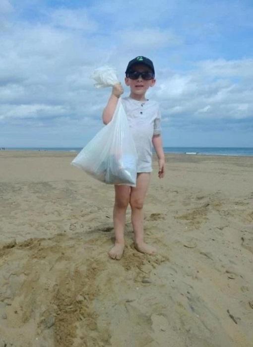 Pequeño paso su día en la playa limpiándola