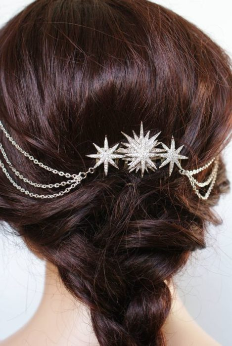Dark-haired girl caught in a bun with star brooches and silver-plated chains