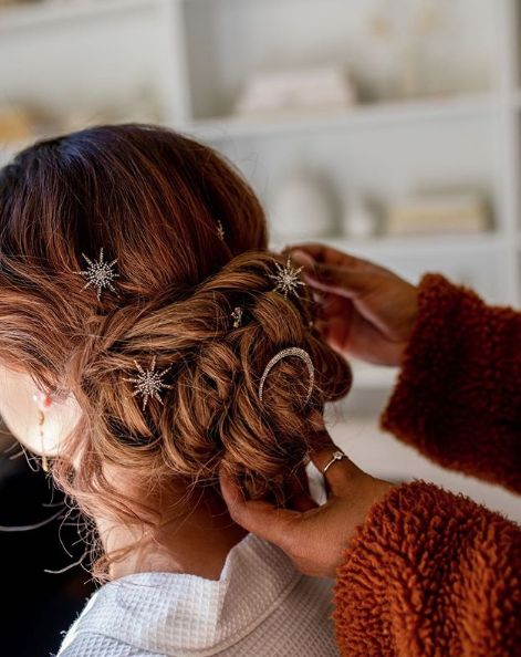 Red-haired bride with low updo and small star-shaped brooches