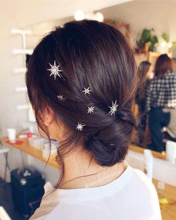 Chica de cabello oscuro agarrado en un chongo con broches de estrella