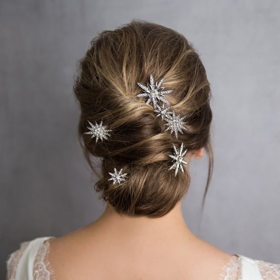 Blonde girl with low bun and accessories in her hair in the shape of stars