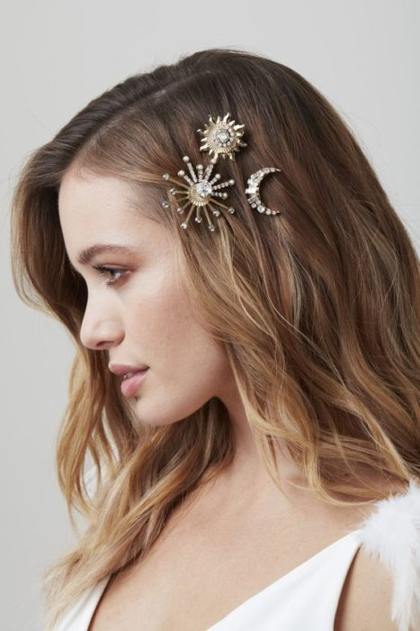 Blonde woman with loose wavy hair wears star and moon barrettes