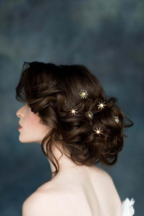 Woman with loose updo and golden star-shaped brooches