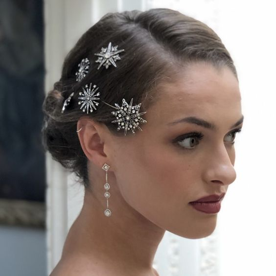 Bride with hair gathered in a low bun with star-shaped brooches