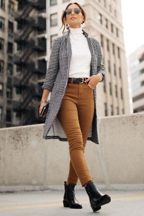 Chica usando blazer de color negro con blanco, blusa blanca, jeans color caki y botines negros