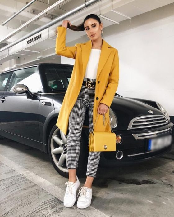 Girl wearing mustard colored blazer, white top and tennis shoes, and black leggings with white