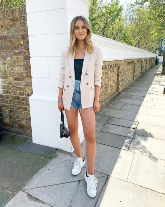 Chica usando blazer de color beige con top negro y short denim y tenis blancos