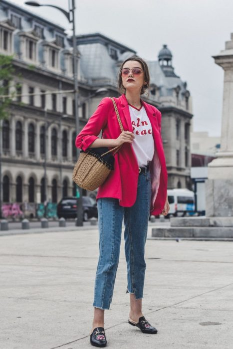 Girl wearing fuchsia pink blazer and white blouse, with denim pants and black mules