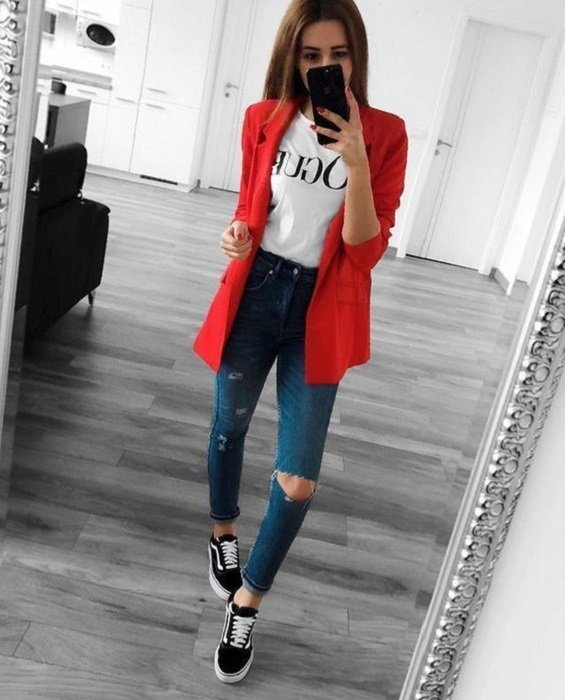 Girl wearing red blazer, with white blouse and ripped denim jeans and vans