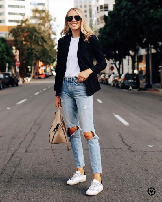 Girl wearing black blazer with white blouse and ripped denim jeans and white tennis shoes