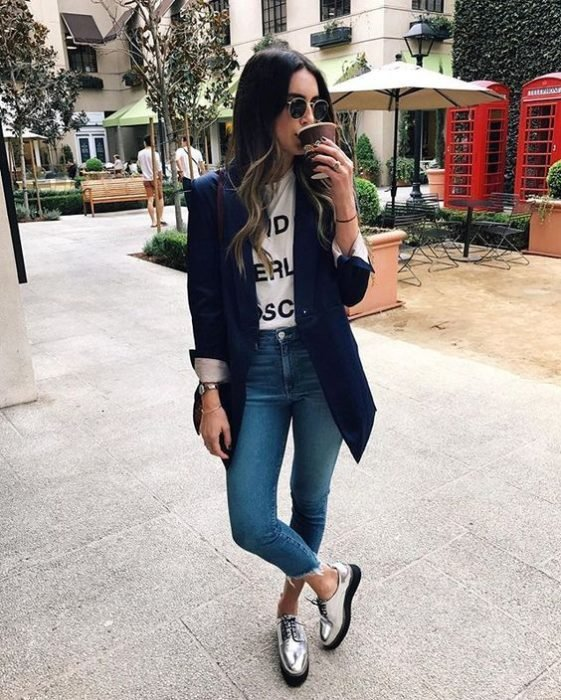 Girl wearing navy blue blazer, with white blouse and denim jeans and silver platform shoes