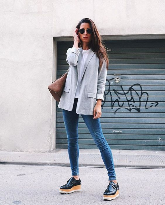 Girl wearing light gray blazer, and white blouse, denim jeans and platform shoes