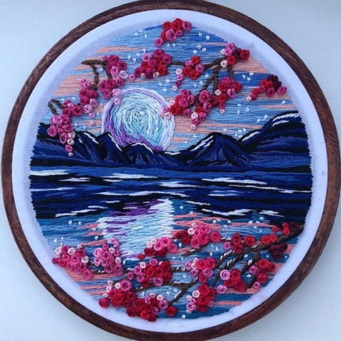 Bordado en aro hecho a mano de una noche despejada, el reflejo del cielo en el agua y flores de cerezo