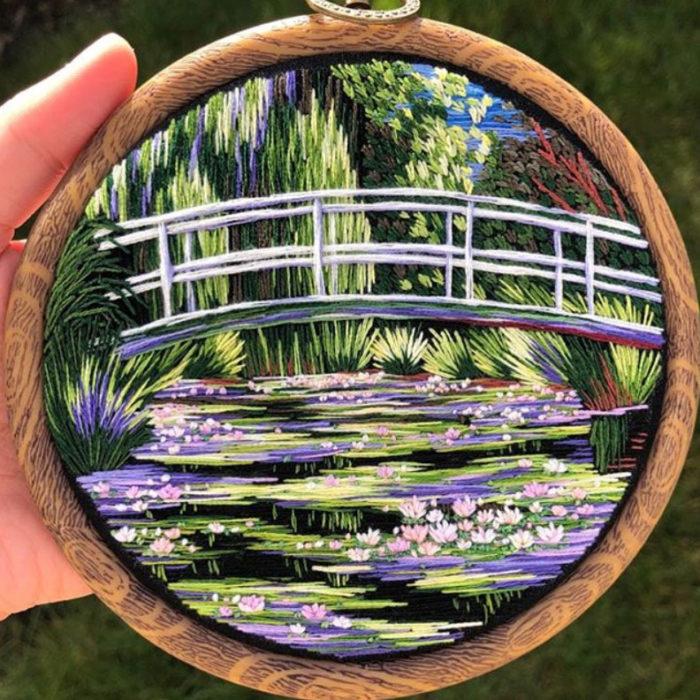 Bordado en aro hecho a mano de un puente que cruza un lago lleno de flores