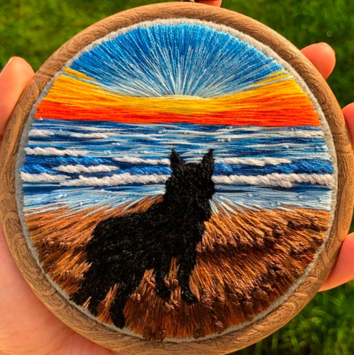 Bordado en aro hecho a mano de un perro en la arena, cerca de la playa