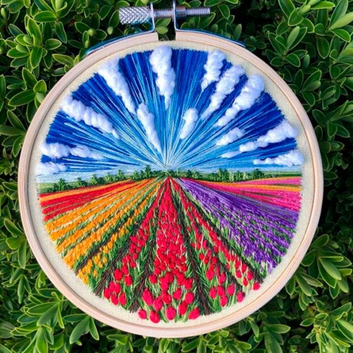 Bordado en aro hecho a mano de un campo de tulipanes de diferentes colores y un cielo despejado