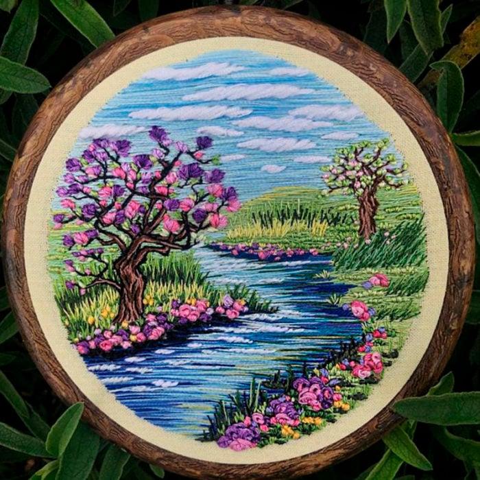 Bordado en aro hecho a mano de un árbol de cerezo a la orilla de un rpio
