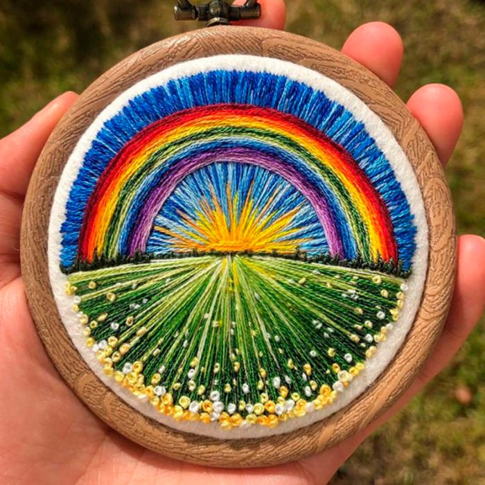 Bordado en aro hecho a mano de un campo de flores y un arcoíris detrás