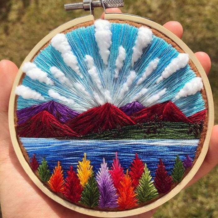 Bordado en aro hecho a mano de unas montañas y un cielo despejado