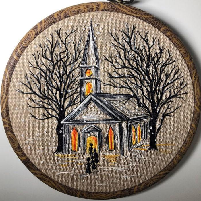 Bordado en aro hecho a mano de una casa con las luces encendidas y cae nieve