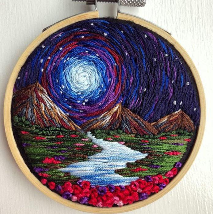 Bordado en aro hecho a mano de una noche estrellada, y un río con flores alrededor