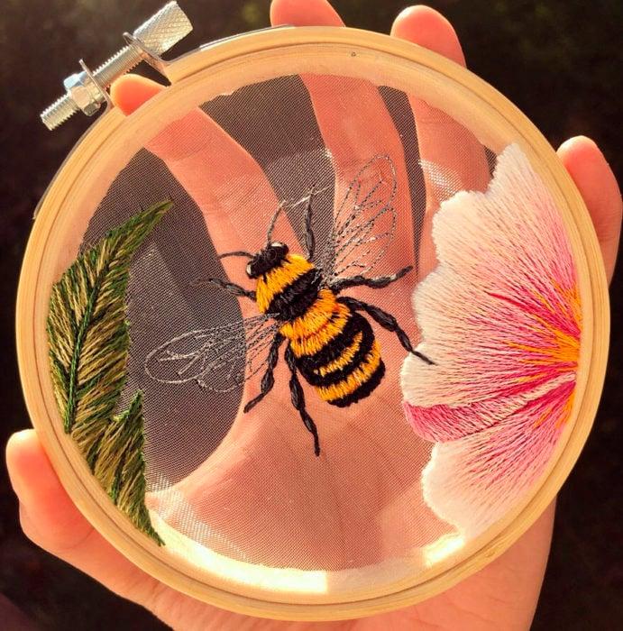 Bordado en aro hecho a mano de una abeja y una flor