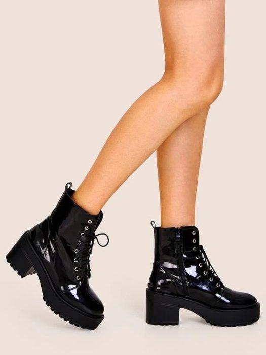 Chica llevando botas antas de charol en tono negro