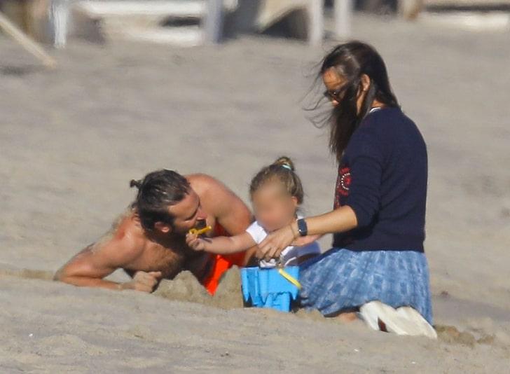 Bradley Cooper y a Jennifer Garden en la playa