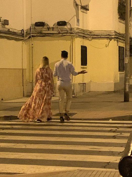Chica y chica caminando por la calle mientras él usa los tacones de ella