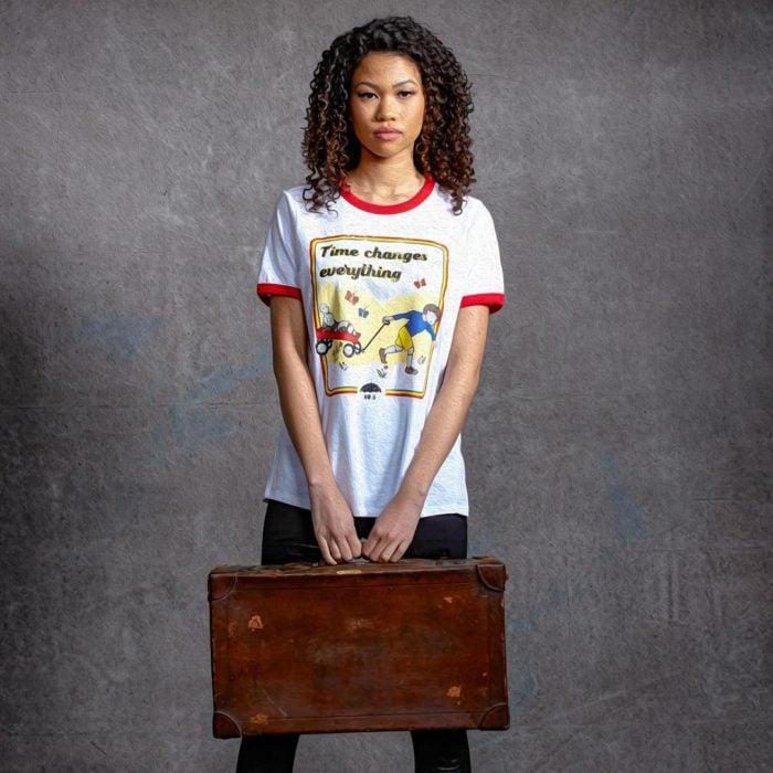 Chica llevando una camisa en colro blanco ocn estampado inspirado en número cinco de la serie The Umbrella Academy