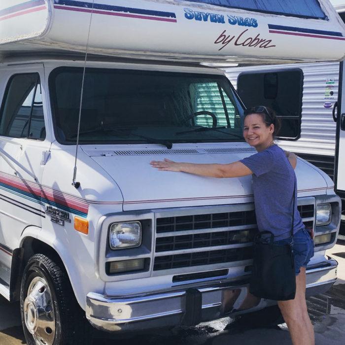 chica abrazando una camioneta van blanca