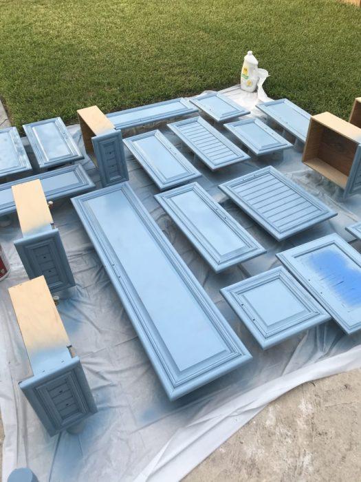 Puertas de madera siendo pintadas de color azul con pintura en spray
