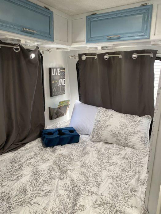 cama montada dentro de una camioneta van con cobijas blancas