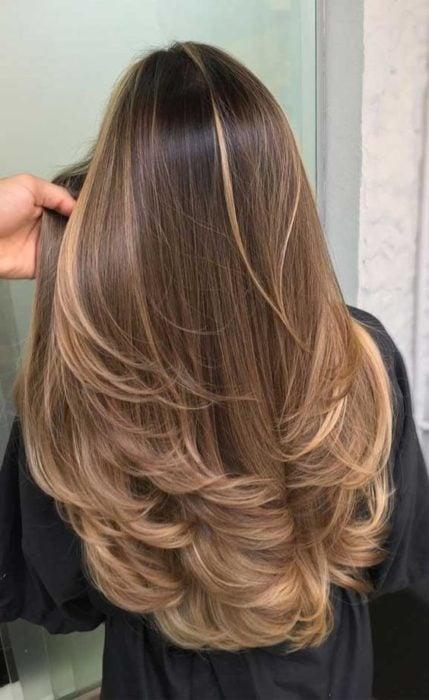 Mujer de cabello castaño claro con corte en capas