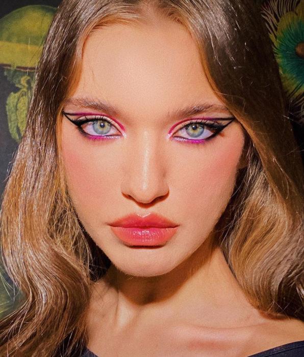 Chica de ojos grises con verde, delineado gráfico de color negro y rosa mexicano, cabello castaño cobrizo ondulado, labios rosas