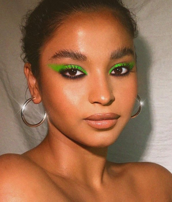 Brunette girl with dark brown hair, brown eyes, lemon green and black eyeshadow, nude lips, golden hoop earrings