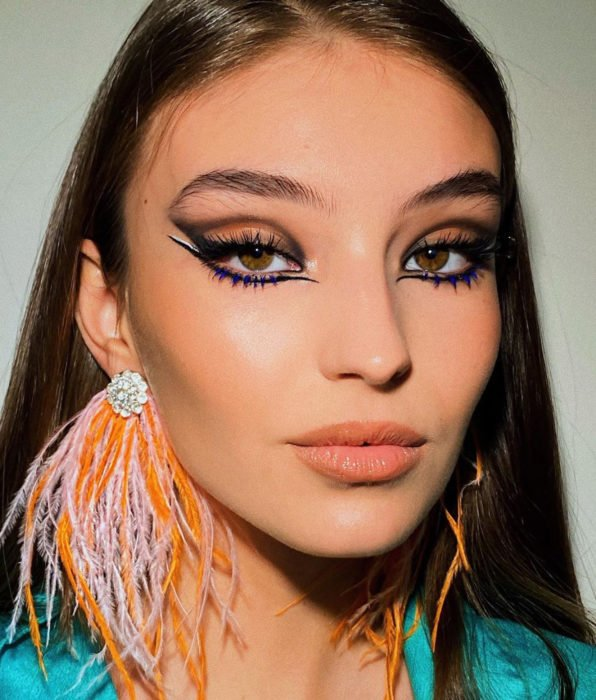 Woman with brown eyes, straight brown hair, party makeup, blurred graphic liner under the eyes, blue lashes, nude lipstick
