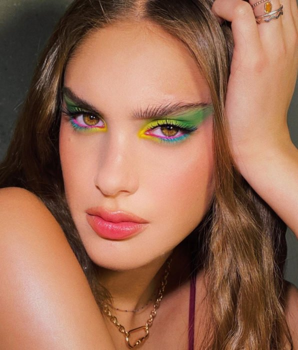Woman with wavy brown hair, brown eyes, rainbow shadows, green, yellow, blue and pink, pink lipstick