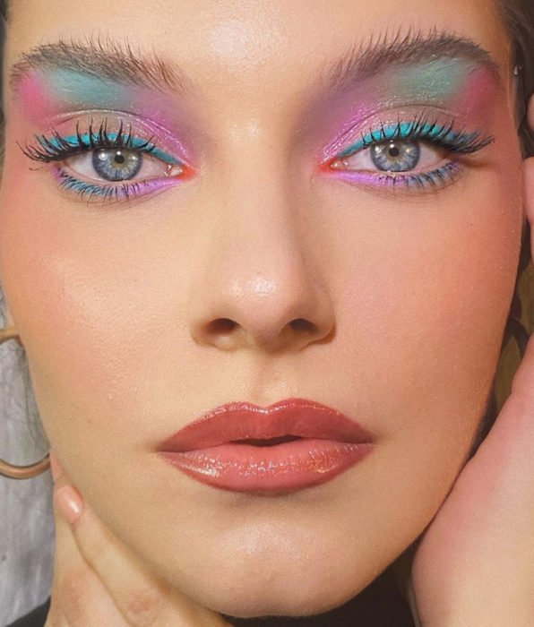 Woman with blue eyes, with pastel feminine makeup, blue and pink shadows, nude lipstick