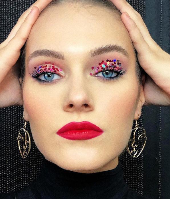 Blue-eyed woman with natural feminine makeup, glitter glitter eyeshadow, red lipstick duerte