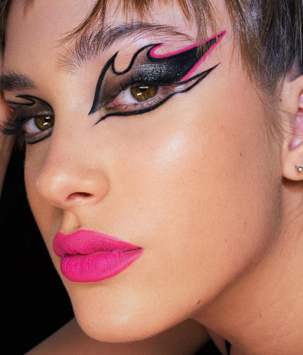 Brunette girl with brown and green eyes, with party makeup, outlined by flames, black with fuchsia pink, Mexican pink lipstick