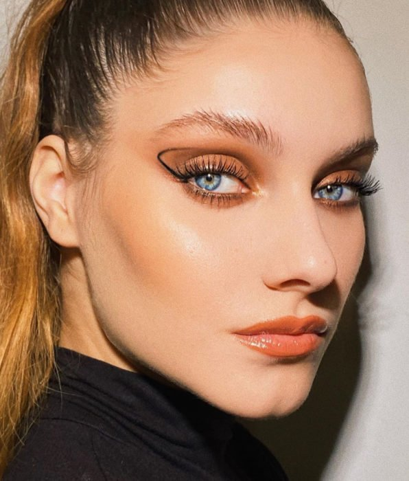 Girl with blue eyes, blonde brown hair in ponytail, natural makeup, graphic liner, orange shadows, peach lips