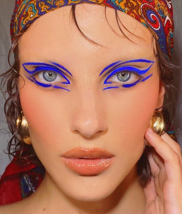 Girl with blue eyes, party makeup, electric blue graphic liner, nude lips